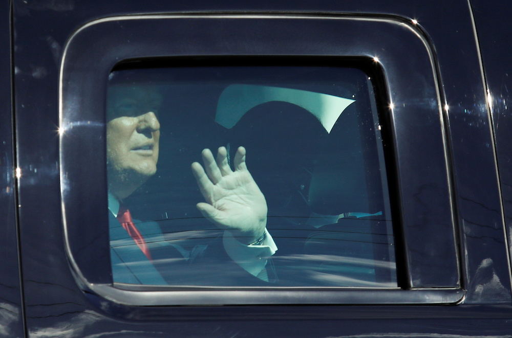 US President Donald Trump waves from a car as he drives past supporters in West Palm Beach, Florida, January 20, 2021. — Reuters pic