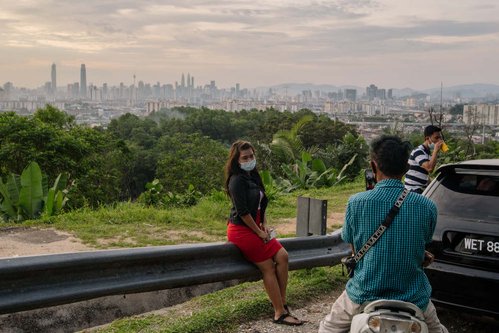 People wearing face masks pose for a picture on the roadside atop a hill with a view of the Kuala Lumpur skyline in Ampang January 31, 2020. — Picture by Firdaus Latif