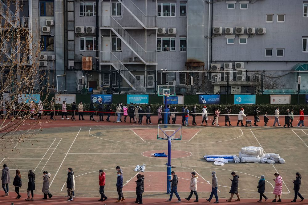 People line up to get their nucleic acid test on the sports ground of a school in Beijing China