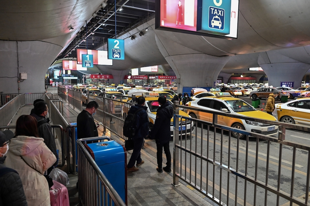 Passengers waiting for taxis outside Wuhan train station in Wuhan in China's central Hubei province. — AFP pic