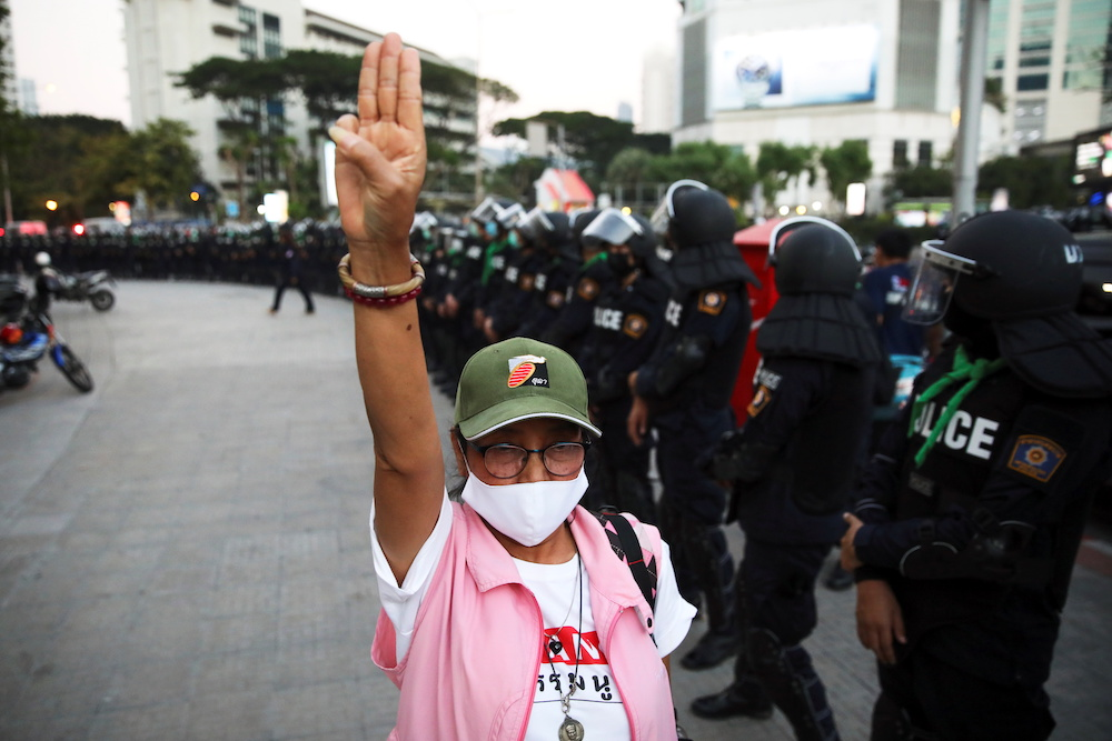 A person flashes a three-finger salute next to police officers during a demonstration demanding to release the people arrested following the anti-government and reforming monarchy protests in Bangkok, Thailand, January 16, 2021. — Reuters pic