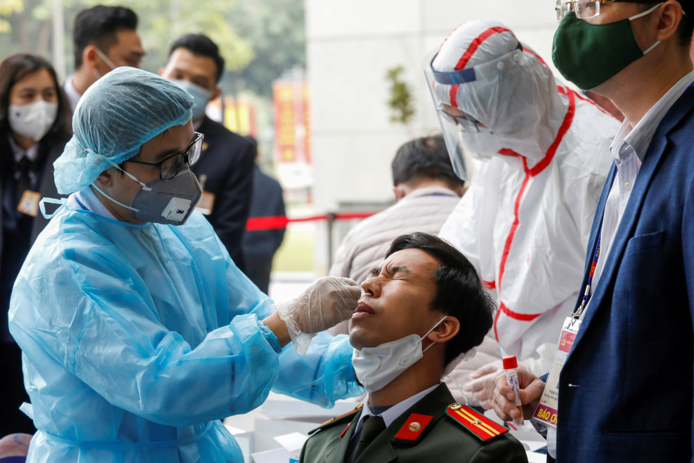 A health worker takes a swab sample from a security officer at the National Convention Centre, the venue for the 13th National Congress of the Communist Party of Vietnam, in Hanoi, Vietnam January 29, 2021. — Reuters pic
