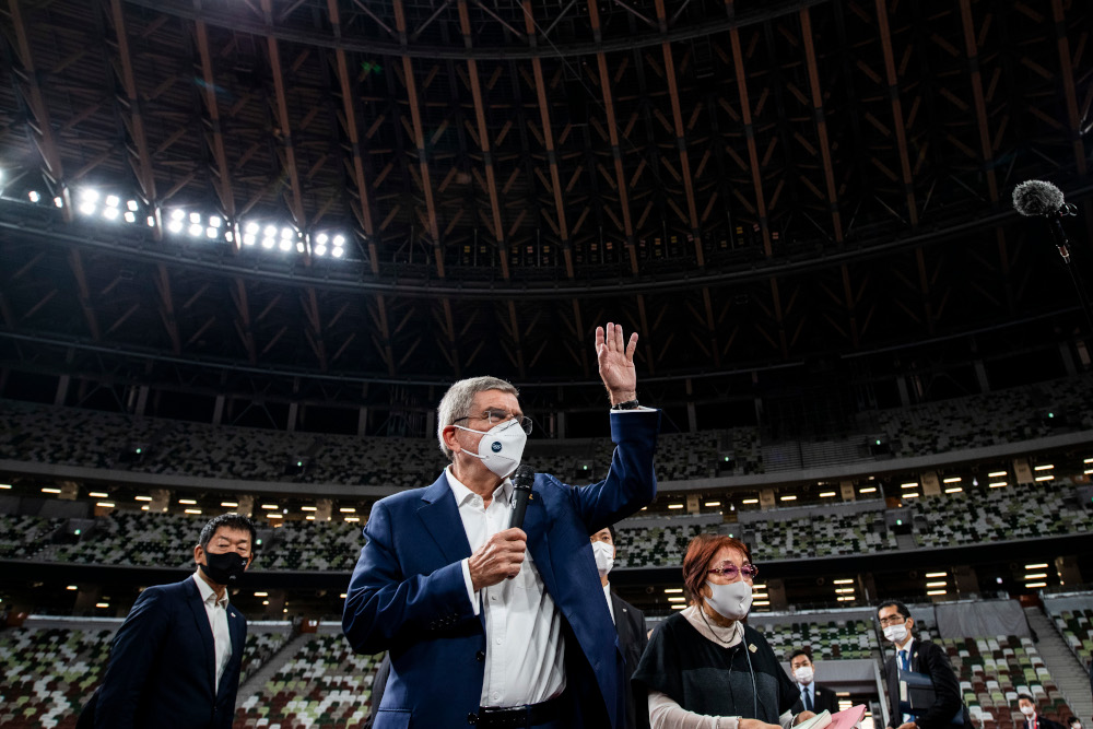 In this file photo taken November 17, 2020 IOC president Thomas Bach waves as he speaks to the media during a visit to the National Stadium, the main venue for the 2020 Olympic and Paralympic Games postponed until July 2021 due to the Covid-19 coronavirus pandemic, in Tokyo. — AFP pic