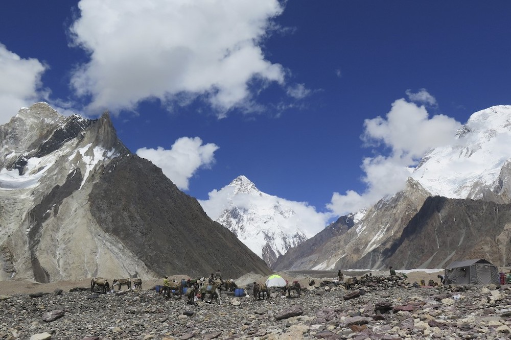 In this file photo taken on August 14, 2019, porters set up tents at the Concordia camping site in front of K2 summit (centre) in the Karakoram range of Pakistan's mountain northern Gilgit region. — AFP pic