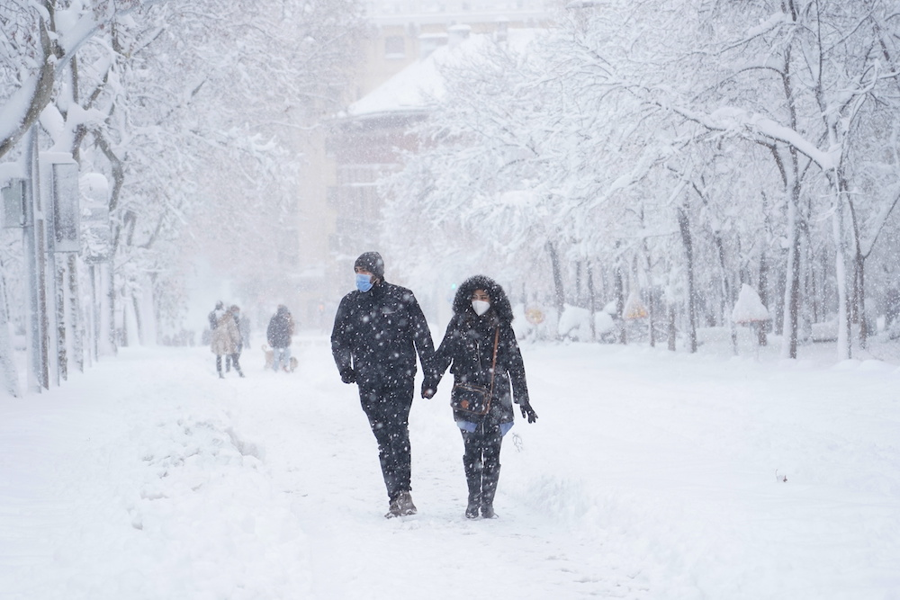 A couple hold hands as they walk on the street during a heavy snowfall in Madrid, Spain, January 9, 2021. — Reuters pic