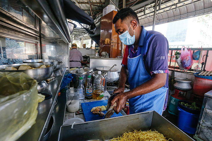 Muhamad Faris preparing the ingredients for 'mee manja' at the stall.