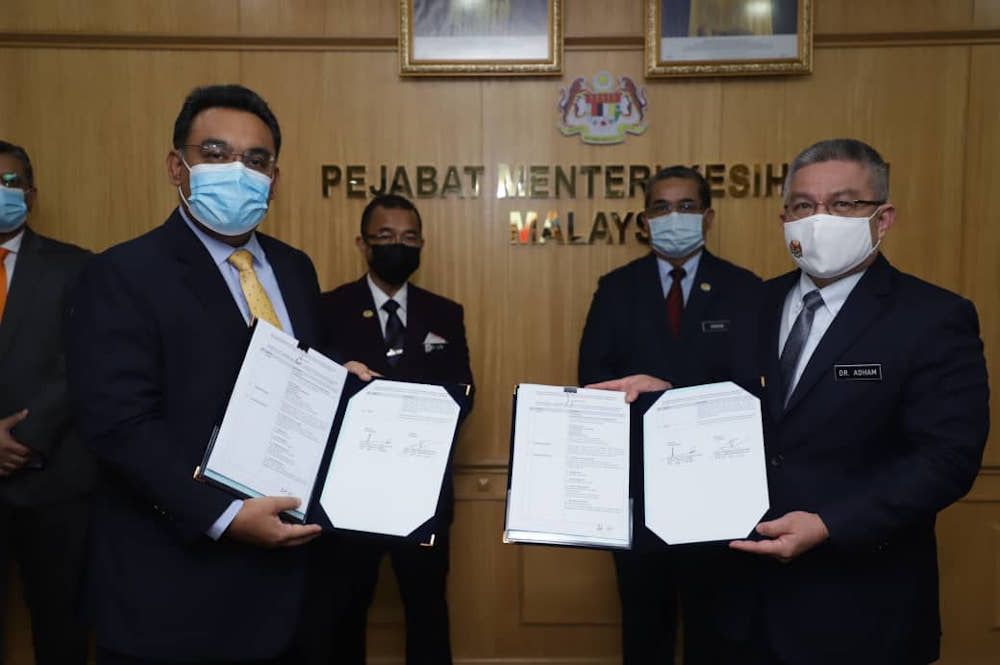 Pharmaniaga group managing director Datuk Zulkarnain Md Eusope and Health Minister Datuk Seri Dr Adham Baba pose after signing the agreement to supply Covid-19 vaccine January 26, 2021.— Picture courtesy of Pharmaniaga