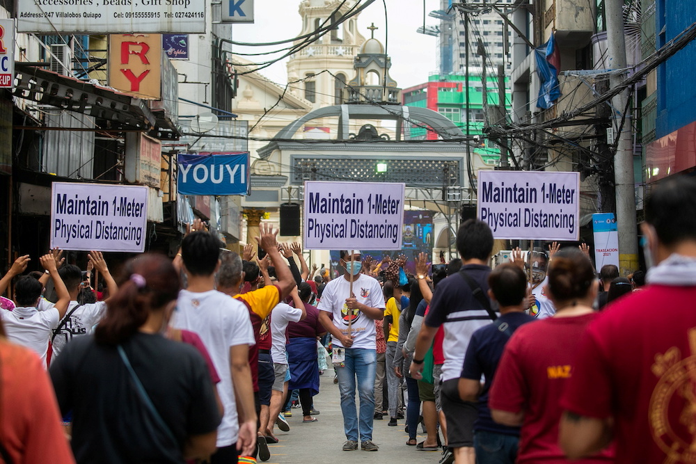 A church worker carries a placard reminding mass-goers to maintain physical distancing to prevent the spread of the coronavirus disease, as Catholic devotees queue to attend mass on the feast day of the Black Nazarene, outside Quiapo Church in Manila, Phi