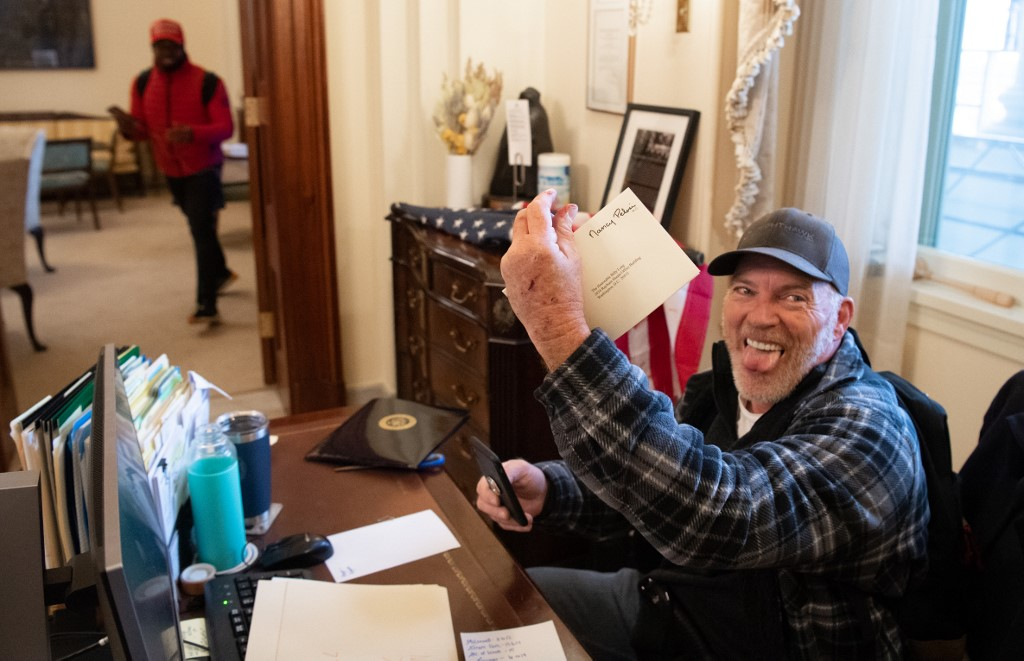 Richard Barnett, a supporter of US President Donald Trump, holds a piece of mail as he sits inside the office of US Speaker of the House Nancy Pelosi after protestors breached the US Capitol in the US Capitol in Washington, DC, January 6, 2021. — AFP pic