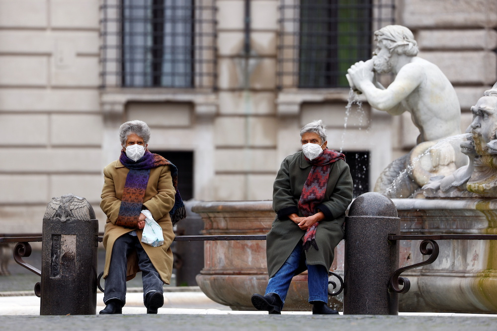 People sit next to a fountain at Piazza Navona as the spread of the coronavirus disease continues, in Rome, Italy January 22, 2021. — Reuters pic