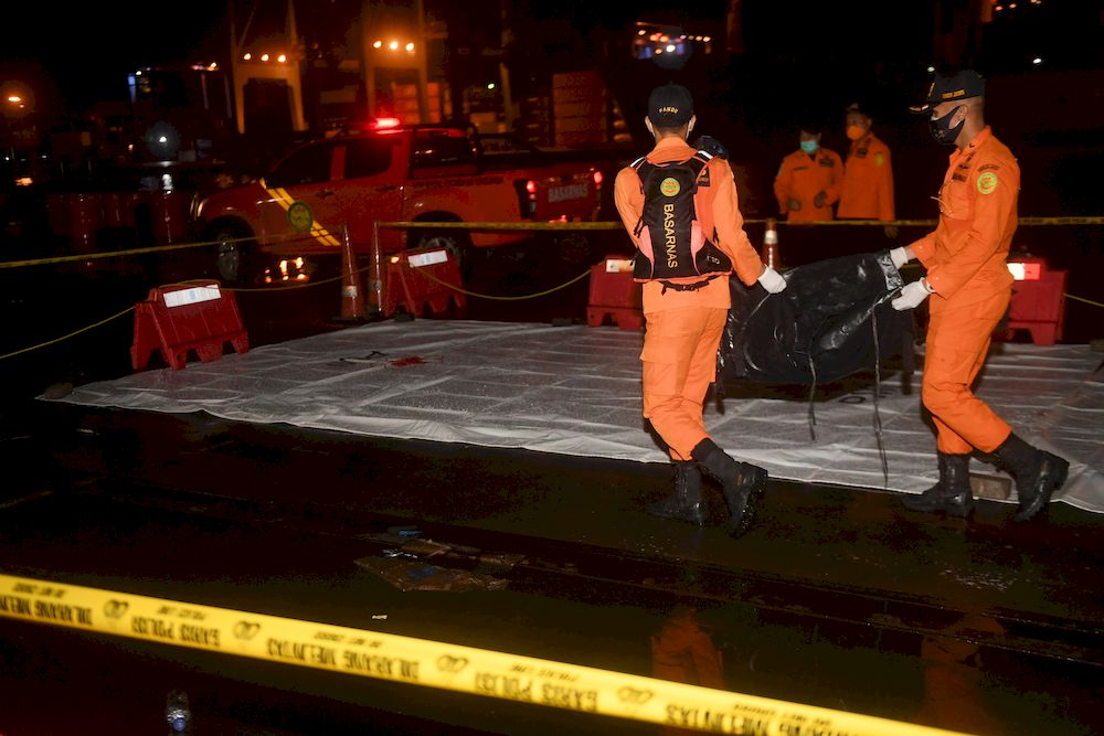 Indonesian rescue members carry a body bag containing suspected remains of the Sriwijaya Air plane flight SJ182 which crashed into the sea, at Jakarta International Container Terminal port in Jakarta, Indonesia, January 9, 2021. — Antara Foto/Akbar Nugroho Gumay pic via Reuters