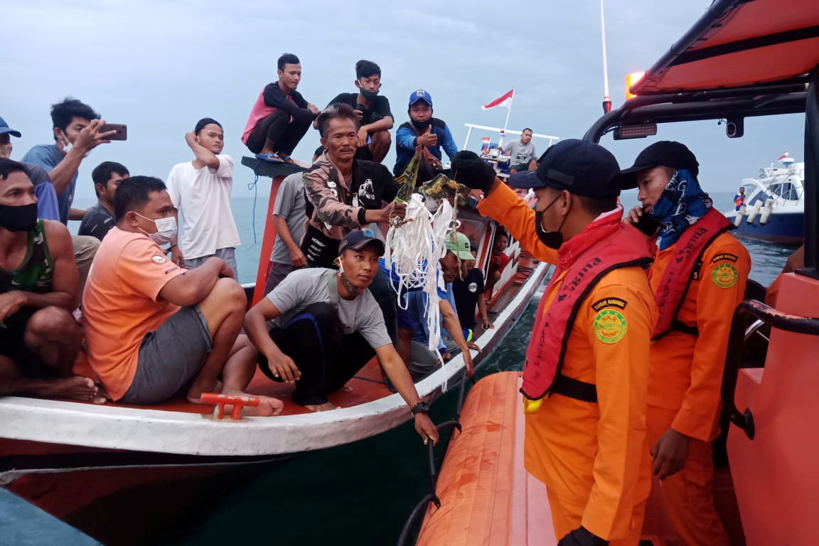 Local fishermen and rescuers hold suspected remains of the Sriwijaya Air plane flight SJ182, which crashed into the sea near Jakarta, Indonesia, January 9, 2021 in this photo taken by Antara Foto. — Antara Foto via Reuters