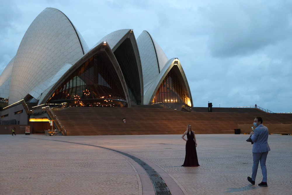 A woman poses for a photo in front of the Sydney Opera House as a small number of people begin celebrating New Year's Eve at the Sydney Harbour waterfront amidst tightened Covid-19 prevention regulations in Sydney, Australia, December 31, 2020. ― Reuter