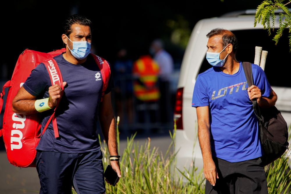 Tennis players and support staff walk from accommodations where they are undergoing mandatory quarantine to train at a nearby facility in advance of the Australian Open in Melbourne January 20, 2021. — Reuters pic