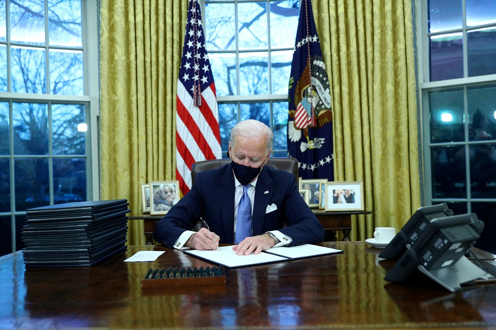 US President Joe Biden signs executive orders in the Oval Office of the White House in Washington, after his inauguration as the 46th President of the United States January 21, 2021. ― Reuters pic