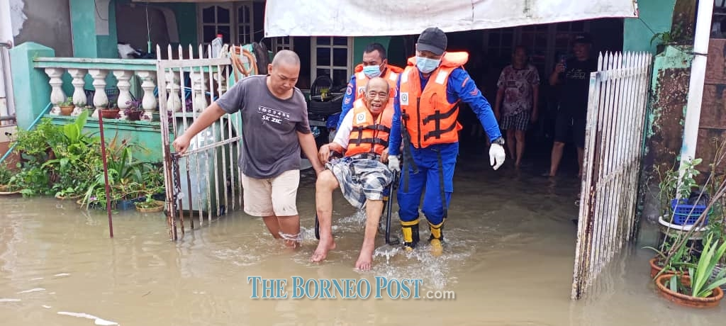 Members from the Civil Defence Force evacuating a flood victim at Taman Malihah this morning. ― Borneo Post pic