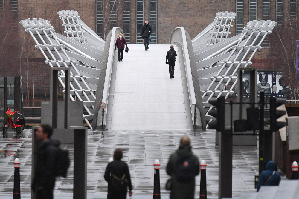People walk across Millennium bridge in central London as Britain is in its third lockdown due to the coronavirus January 12, 2021. Since first being reported to the WHO on December 14, the British-identified variant VOC 202012/01 has been found in 50 countries, territories and areas, the agency said. — AFP pic