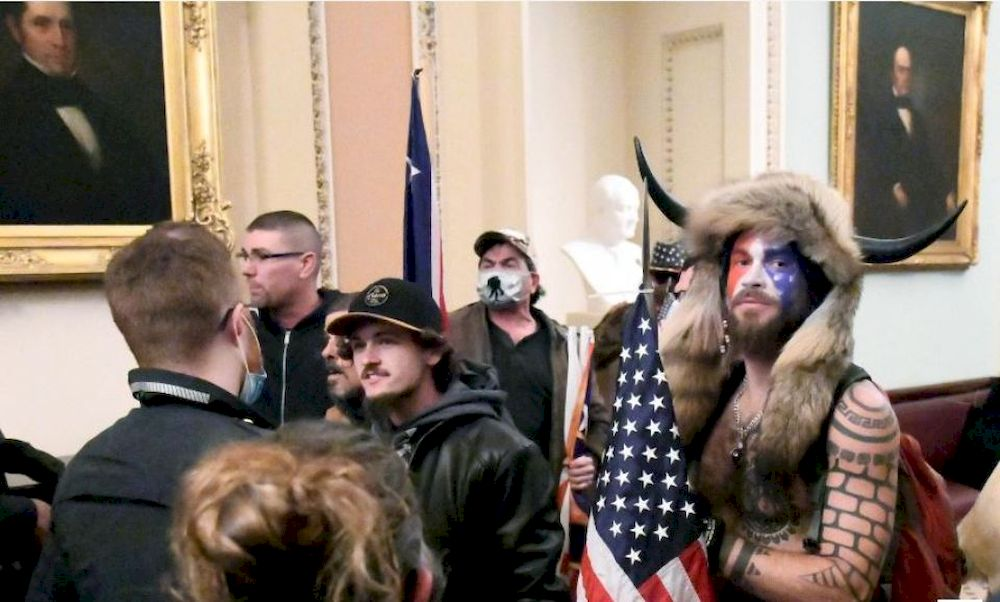 Jacob Anthony Chansley, also known as Jake Angeli, of Arizona, stands with other supporters of US President Donald Trump as they demonstrate on the second floor of the US Capitol near the entrance to the Senate after breaching security defences, in Washin
