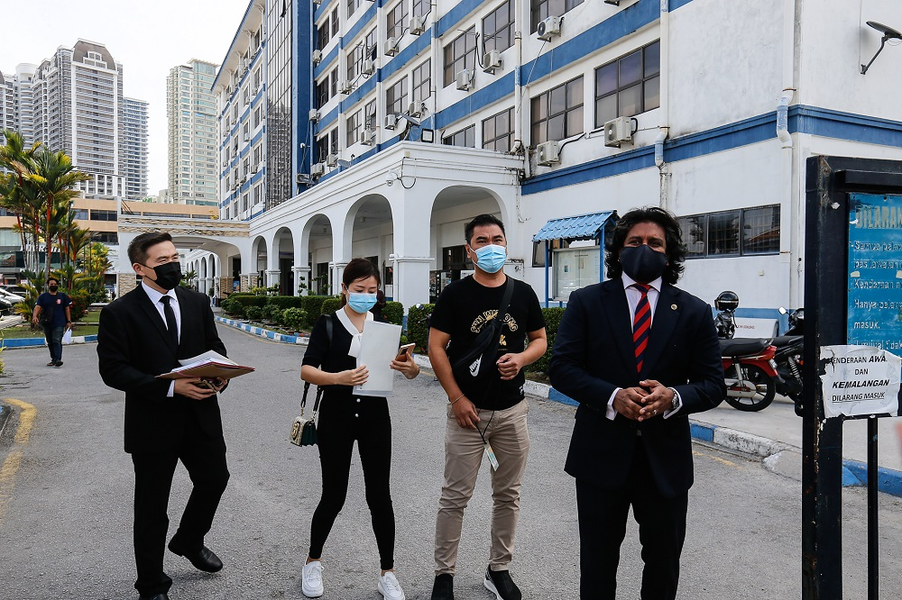 Lawyer Dev Kumaraendran (right) escorting 41-year-old man (second right) and his wife George Town district police headquarters at Jalan Patani, January 13, 2021. ― Picture by Sayuti Zainudin