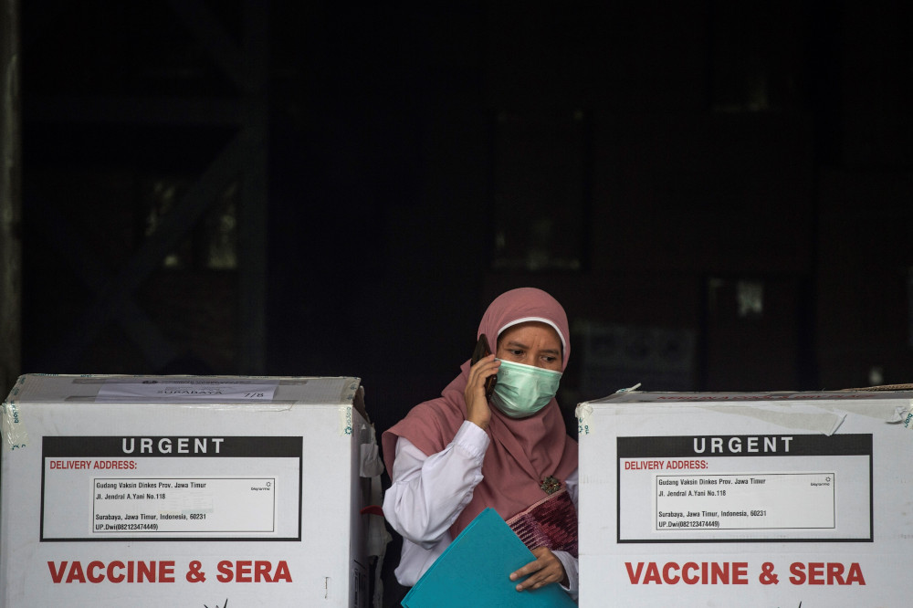 A health worker checks the containers of Covid-19 vaccine produced by China's Sinovac, as they arrived in Surabaya January 13, 2021. — AFP pic