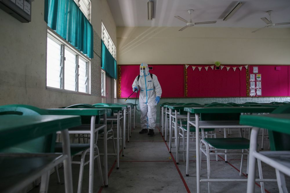 A Fire and Rescue personnel sprays disinfectant at Sekolah Rendah Agama Kota Damansara 5 on January 19, 2021. A total 15 schools in Terengganu have been ordered to close due to Covid-positive cases. — Picture by Yusof Mat Isa