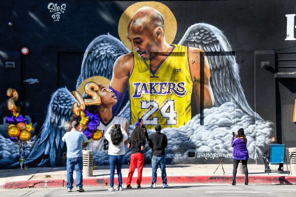 Fans gather at a mural of Kobe Bryant and his daughter Gianna painted on the wall of Hardcore Fitness Bootcamp gym in downtown Los Angeles January 26, 2021. — Reuters pic