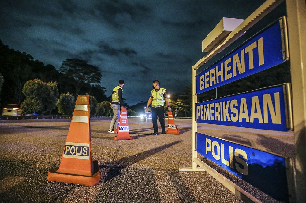 Police officers man a roadblock at the Gombak Toll Plaza, January 12, 2021. The current MCO will span January 13 to January 26. ― Picture by Hari Anggara