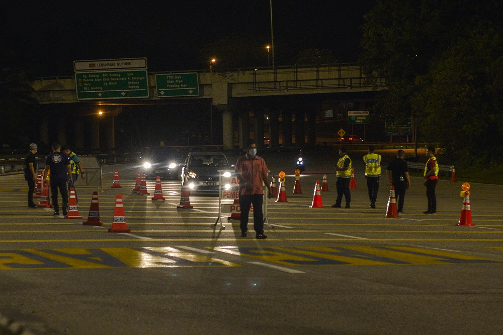 Police man a roadblock on the first day of the movement control order (MCO) in Shah Alam January 13, 2021. ― Picture by Miera Zulyana