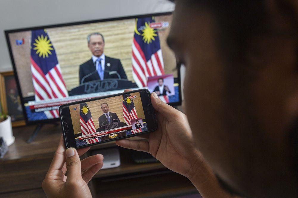 A man watches a live telecast of Prime Minister Tan Sri Muhyiddin Yassin's speech in Kuala Lumpur January 12, 2020. — Picture by Miera Zulyana