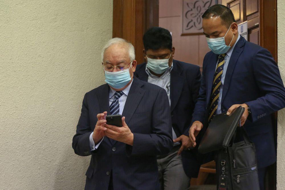 Datuk Seri Najib Razak checks his phone at the Kuala Lumpur High Court January 6, 2021.  — Picture by Yusof Mat Isa