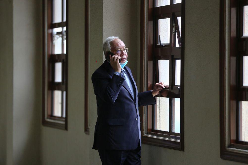 Datuk Seri Najib Razak speaks on his phone at the Kuala Lumpur High Court January 6, 2021.  — Picture by Yusof Mat Isa