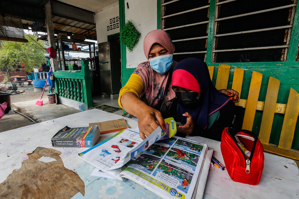 Nurifamanina Abdul Muiz gets help from her grandmother Fatimah Din as she does her online homework on Pulau Aman January 22, 2021. — Picture by Sayuti Zainudin