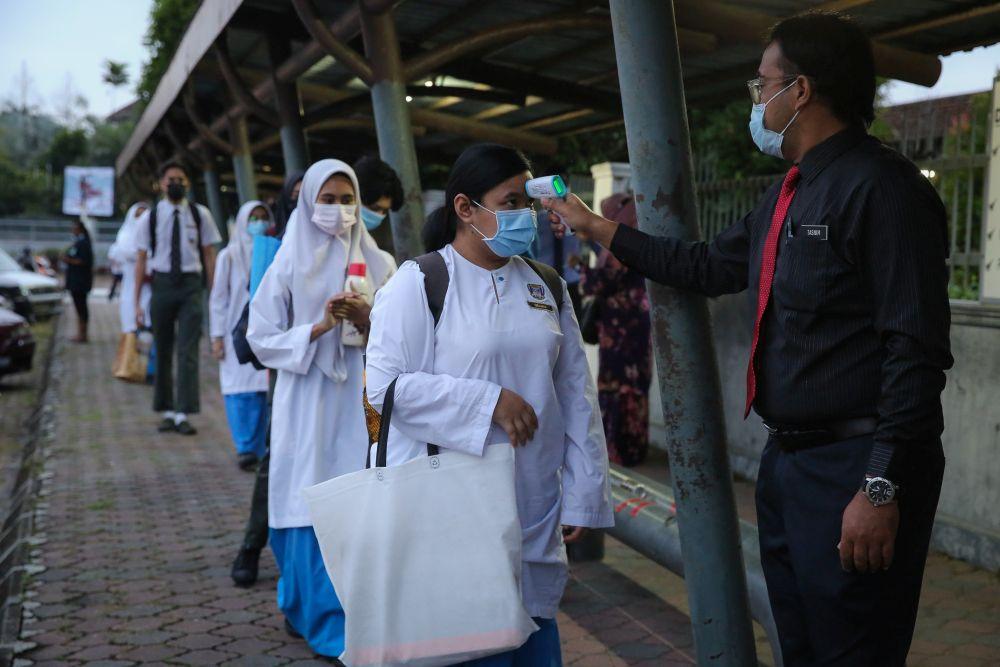 Students wait to have their temperature taken at Sekolah Menengah Kebangsaan Bukit Jelutong in Shah Alam January 20, 2021. — Picture by Yusof Mat Isa