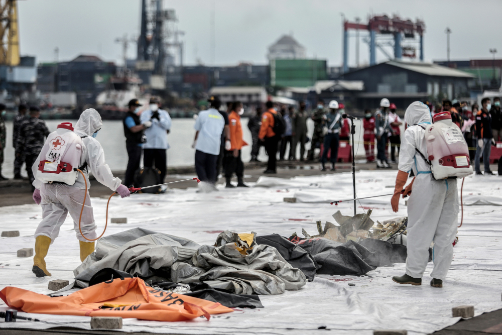 Health workers spray disinfectant over body bags containing human remains recovered from the crash site of Sriwijaya Air flight SJ182 at the port in Jakarta January 10, 2021. — AFP pic