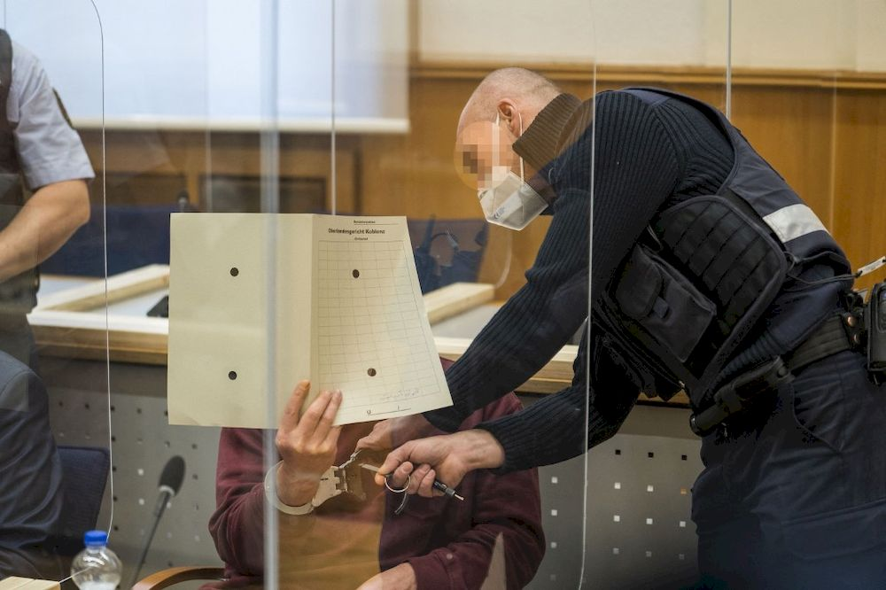 A justice official removes the handcuffs of Syrian defendant Eyad al-Gharib, accused of crimes against humanity, as he waits to hear the verdict in the court room, February 24, 2021 in Koblenz, Germany. — AFP pic
