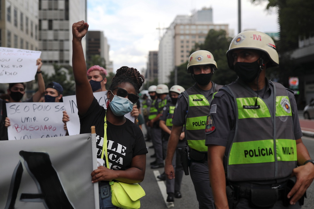 Demonstrators stand next to police officers during a protest against Brazil's President Jair Bolsonaro and his handling of the coronavirus disease (Covid-19) outbreak, in Sao Paulo, Brazil, January 31, 2021. — Reuters pic