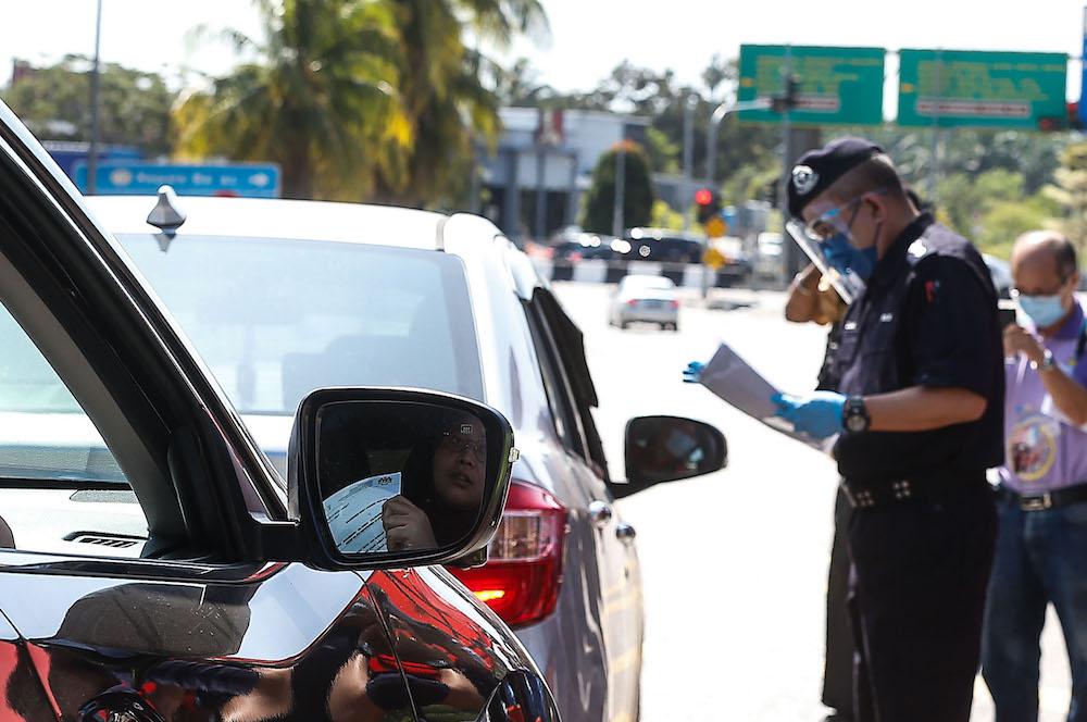 Northern Seberang Perai District Police Chief ACP Noorzainy Mohd Noor speaks to a motorist at a roadblock near the Bertam Toll Plaza, February 5, 2021. — Picture by Sayuti Zainudin