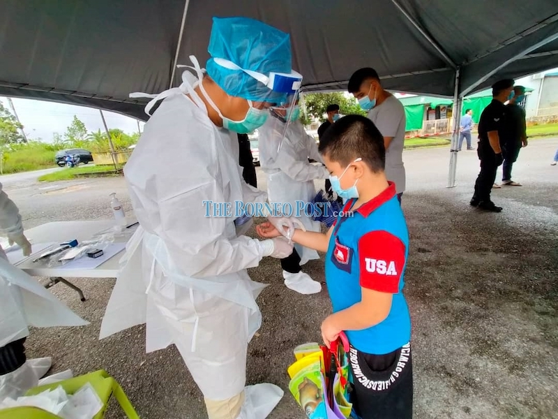 A health worker fixing a white wristband on one of the individuals who had underwent swab test today. — Borneo Post Online pic