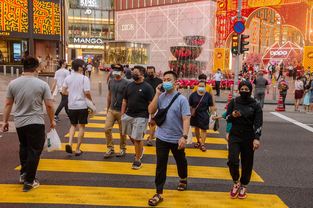 People wearing facemasks cross the road in front of Pavilion in Bukit Bintang amid the movement control order in Kuala Lumpur February 16, 2021. — Picture by FIrdaus Latif