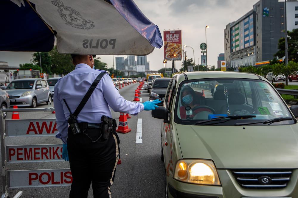 Police officers conducting checks at a roadblock in Sungai Besi, Kuala Lumpur February 16, 2021. — Picture by Shafwan Zaidon