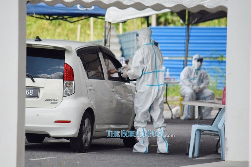 File picture shows medical personnel conducting health checks at Taman Univista where a cluster has emerged. — Borneo Post Online pic