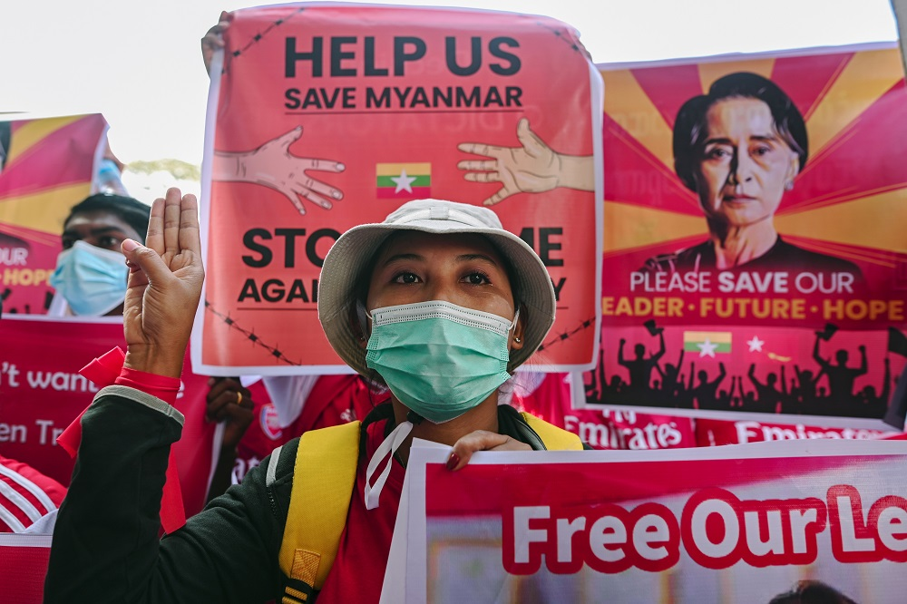 A demonstrator flashes a three-finger salute while holding a sign to protest against the military coup and demand for the release of elected leader Aung San Suu Kyi, in Yangon February 12, 2021. — Reuters pic