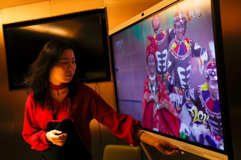 Liu Yuting controls the screen while watching the Lunar New Year gala after having dinner with her family at a Haidilao hotpot restaurant, in Beijing February 11, 2021. — Reuters pic