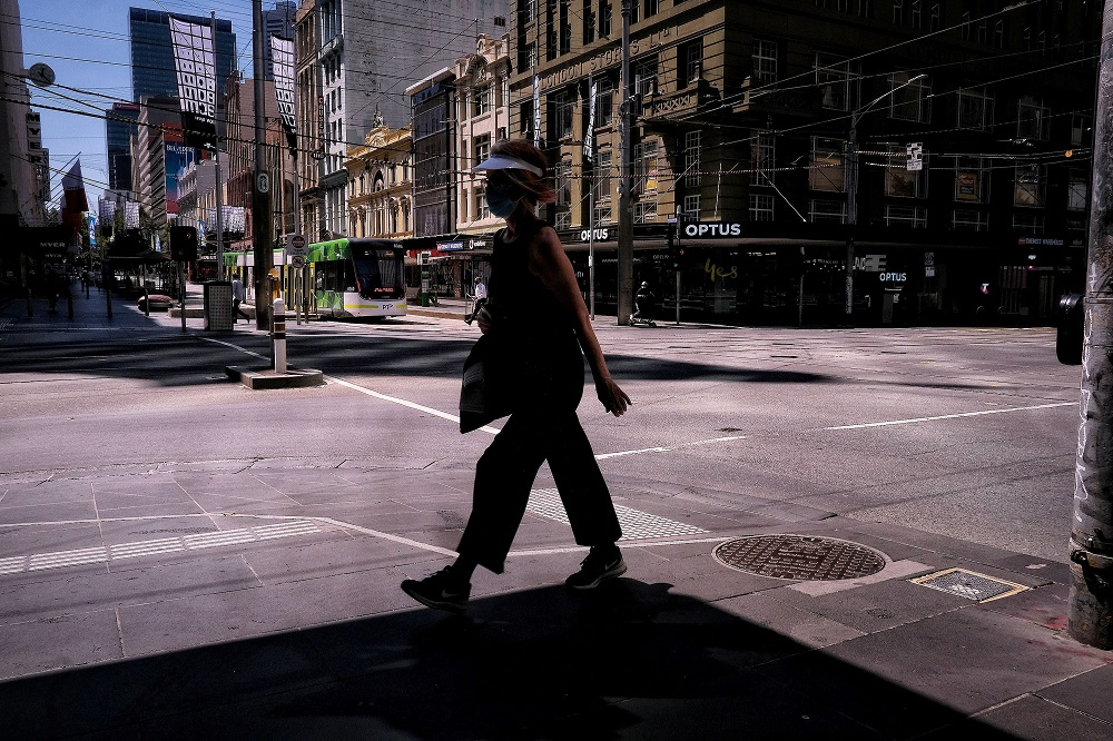 A woman walks on a street, amid a state-wide lockdown, in Melbourne city centre, Victoria February 15, 2021. — AAP Image/Luis Ascui/via Reuters
