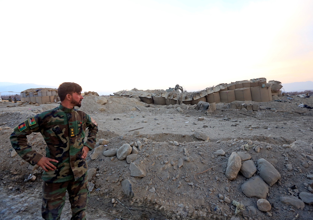 An Afghan National Army soldier inspects the site of a car bomb attack on a military base in Shirzad district of Nangarhar province, Afghanistan January 30, 2021. — Reuters pic