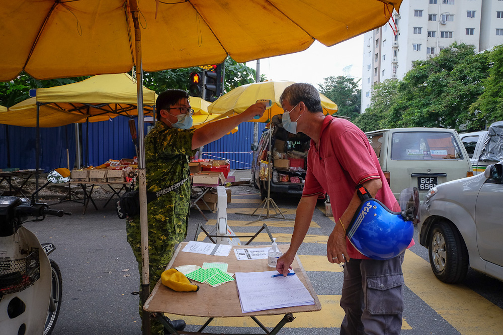 A People's Volunteer Corps (Rela) member checks the temperature of people at the entrance of the Taman Desa Phase 1 night market in Kuala Lumpur February 5, 2021. — Picture by Yusof Mat Isa