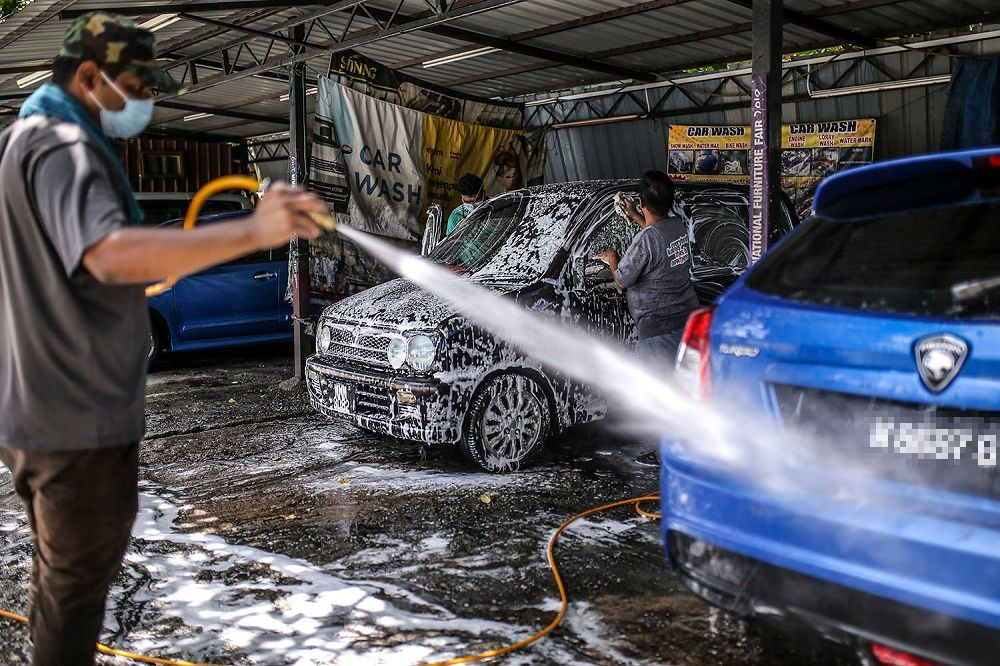 Staff at a car wash centre are seen hard at work in Kuala Lumpur February 6, 2021. — Picture by Hari Anggara