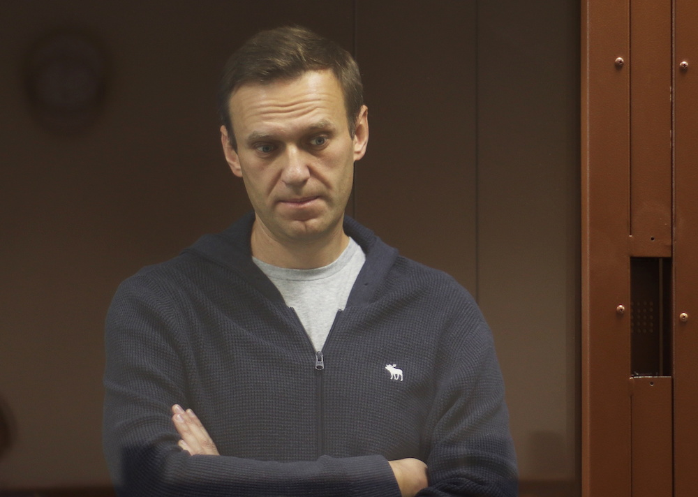 Kremlin critic Alexei Navalny, who is accused of slandering a Russian World War Two veteran, stands inside a defendant dock during a court hearing in Moscow, Russia, Russia February 12, 2021. — Reuters pic