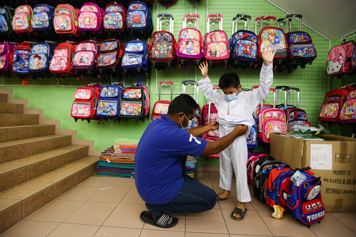 A parent shop for new school essentials for his child in Shah Alam February 20, 2021. — Picture by Yusof Mat Isa