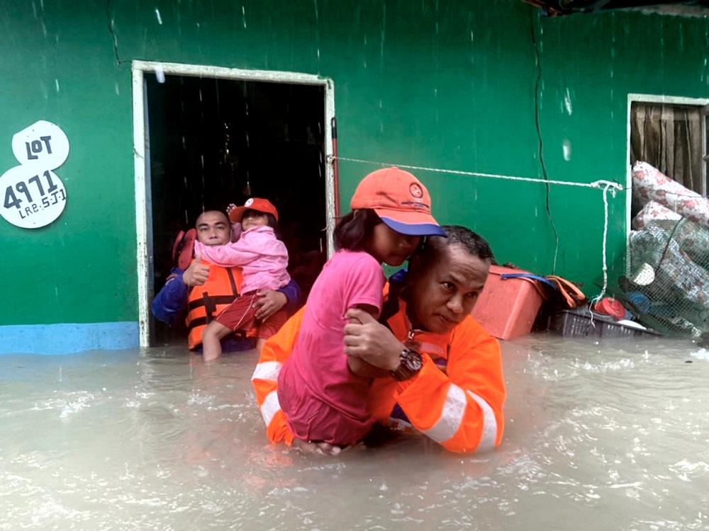 Residents of Kampung Sinar Budi in Batu Kawa are assisted out of their flood-hit homes in Kuching February 19, 2021. — Bernama pic
